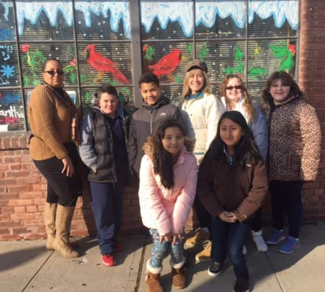 Postmaster Penny Jackson (Far Left) and Buchanan - Verplanck Elementary School Art Teacher Kathy Irwin (Back Row - 3rd from right) admire the fourth and fifth grades student's holiday artwork on the Post Office front window.