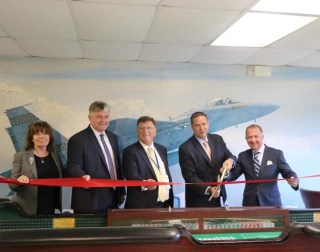 Local officials celebrate the ribbon cutting at the new dealer school at Stewart Airport.