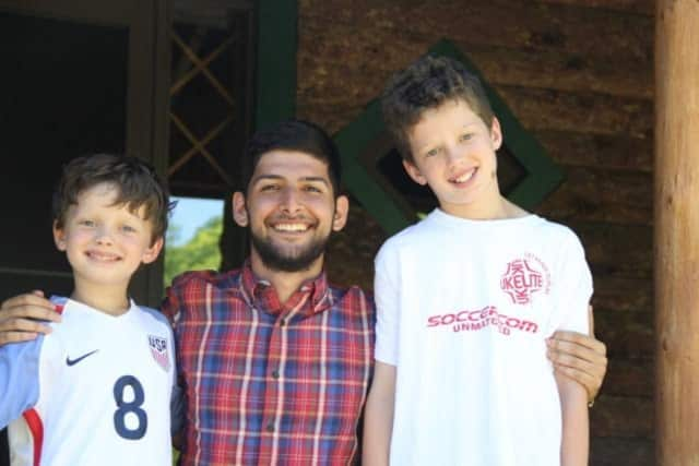Jackson (left) and Gray (right) Scarlett with their au pair, Ali Hoseinzadeh, who is nominated for an international award.