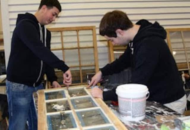 Students from Richie Thomas' glass work reglazing windows from a historic barn at the Hart's Brook Park and Preserve.