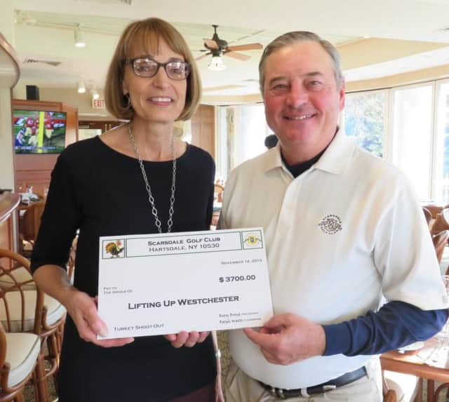 Chris Schwartz, left, director of development for Lifting Up Westchester, receives check from Ralph Watts, tournament chair for the Turkey Shoot Out at Scarsdale Golf Club.