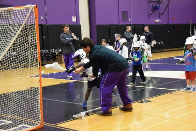 John Jay varsity lacrosse player Jack Gorman shows proper shooting technique to a recruit at John Jay Youth Lacrosse's new player clinic in Cross River on Saturday, Jan. 21.
