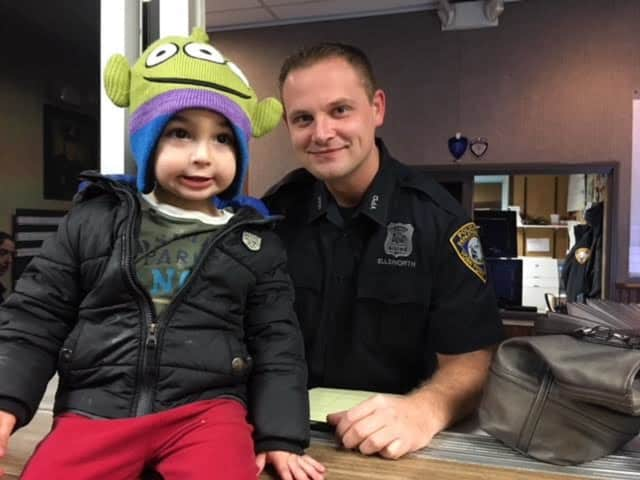 Landon Pruyne, 3, poses with a Yorktown police officer after turning in a wallet he found.
