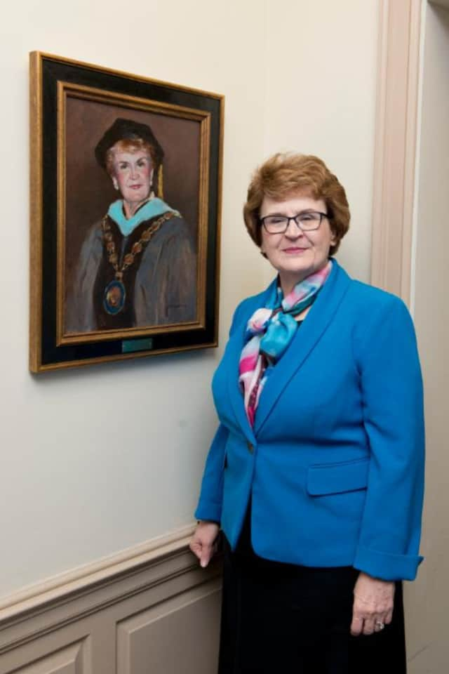 Dr. Martha Shouldis with her portrait at the unveiling at St. Vincent's College in Bridgeport.