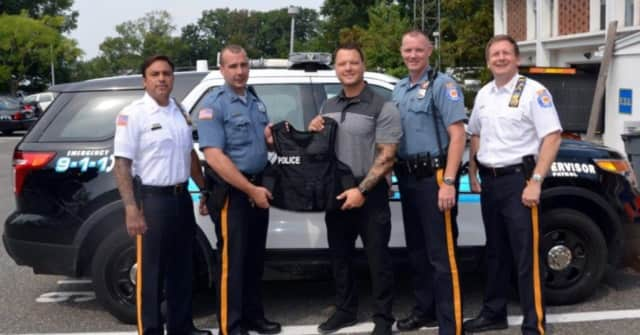 Deputy Chief Guidetti, far left, and Chief Kenneth Ehrengberg, far right, and their officers get a new bulletproof vest.