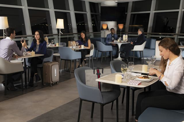 Air France air travelers flying from John F. Kennedy International Airport in Queens to Paris opt for the night service of dinner in the lounge so they can sleep throughout their night flight.