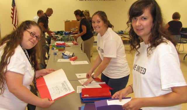 Volunteers stuff folders and backpacks during a prior United Way school-supplies event.