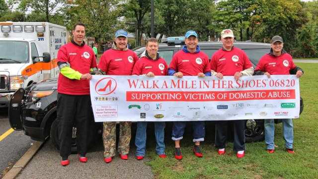 Members of the Darien Police Department walked a mile in red high heels to raise awareness and support victims of domestic violence.