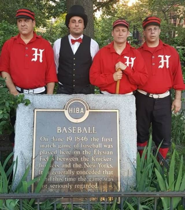 Members of the Hoboken Nine Vintage Base Ball Club stand with a historic marker.