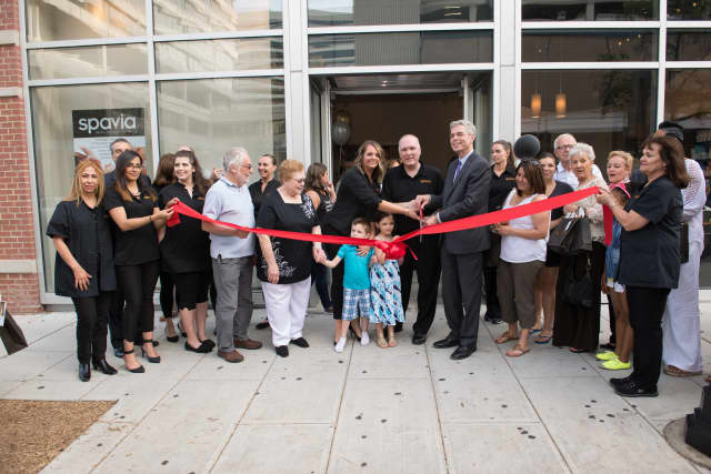 White Plains Mayor Tom Roach assists spavia owners Mike and Maria Hourigan with the ribbon cutting ceremony for the new spa location in White Plains on Main Street.