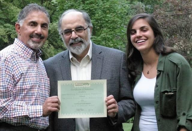 Dennis Tarzian, left, of Fund for Armenian Relief, accepts the donation from Barry Halejian and Sarah Halejian.
