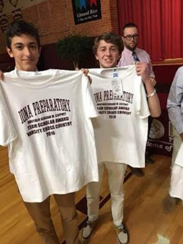 Junior Nick Mingione and sophomore Finn Barron, members of the Iona Prep Varsity Cross-Country Team, pose with their new team scholar award shirts.